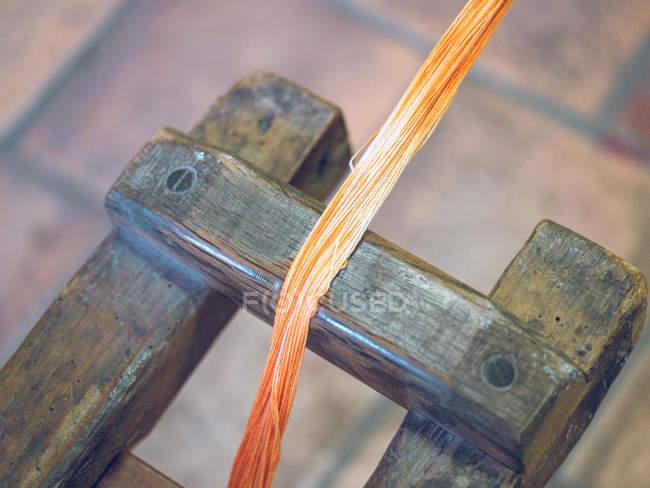 Крупним планом помаранчеві нитки на Ткацький верстат на заводі — стокове фото