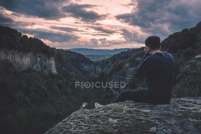 Мужчина с фотокамерой сидит на горе с великолепным закатом — стоковое фото