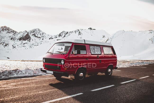 Червоний караван їде біля засніжених гір. — стокове фото