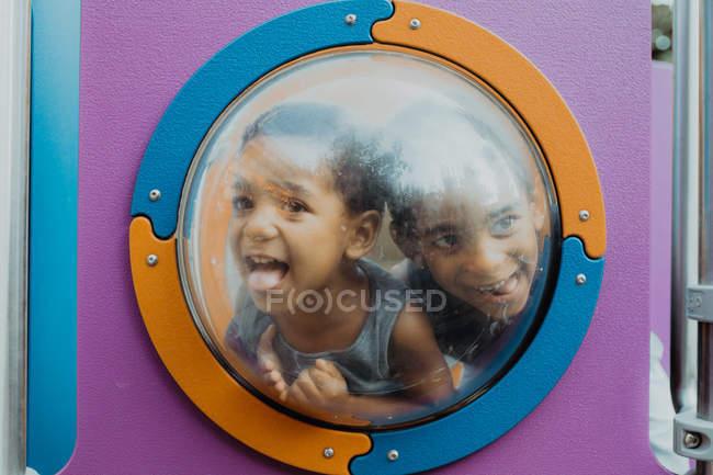 Два маленьких афроамериканских мальчика смотрят в иллюминатор и делают смешные лица, играя вместе на детской площадке — стоковое фото