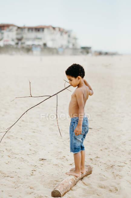 Des jambes sales d'un enfant noir méconnaissable marchant sur une plage de sable — Photo de stock