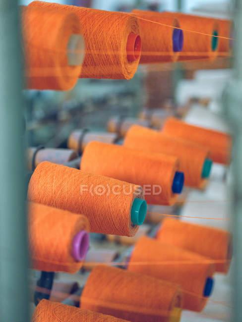 Шпулі з помаранчевою ниткою кріпиться до промислового ткацького верстата на заводі — стокове фото
