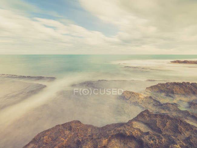 Rocky coast and blue foamy sea on background of sky with clouds — Stock Photo