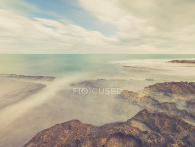 Скелястий берег і блакитні моря пінний на тлі неба з хмарами — стокове фото