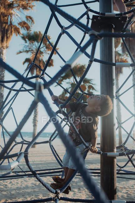 Joyeux garçon afro-américain riant et levant les yeux tout en étant assis sur le filet sur l'aire de jeux sur la plage — Photo de stock