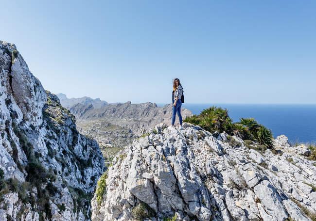 Jeune femme debout sur la falaise — Photo de stock