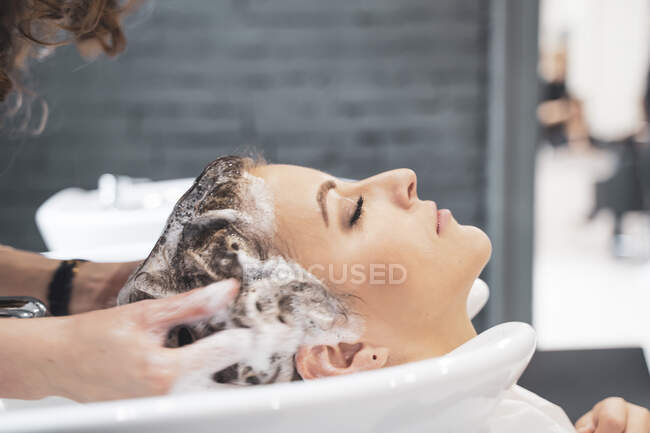 Stylist washing hairs to young lady — Photo de stock