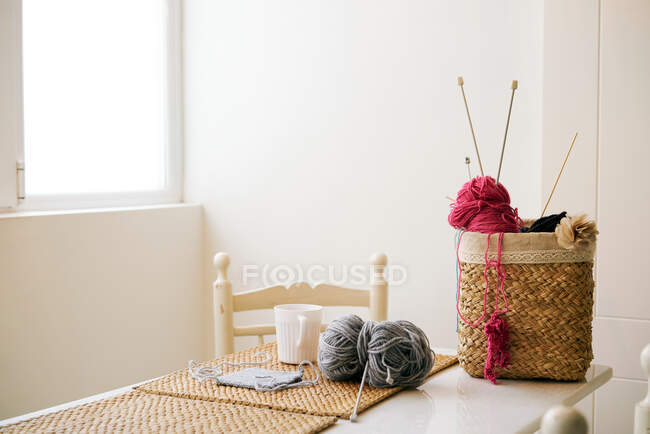 Xícara de chá quente colocado na mesa perto da cesta com fios de tricô e agulhas no quarto acolhedor — Fotografia de Stock