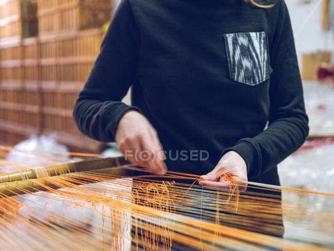 Руки человека, держащего нити на ткацком станке на заводе — стоковое фото