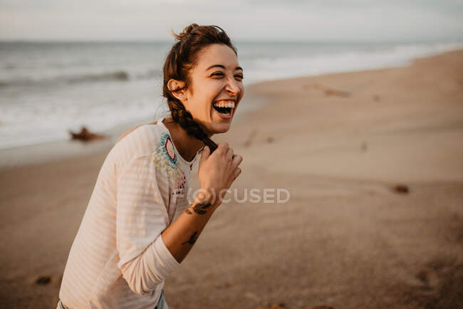 Young lady in casual outfit touching braid and laughing out loud while standing on sandy seashore — Stock Photo