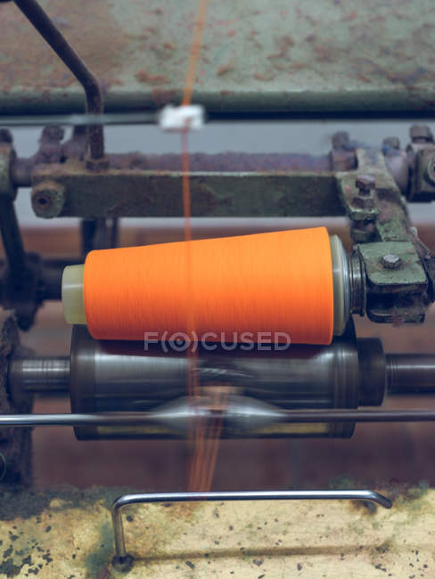 Close-up of orange thread spinning on machine — Stock Photo