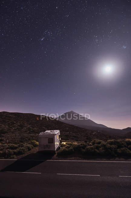 Кемпер причепом припаркований на дорозі віддаленої пустелі під приголомшливим світяться місяця і зоряне небо — стокове фото