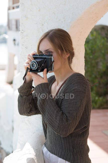 Крупным планом молодая женщина сфотографировалась с винтажной камерой с террасы — стоковое фото