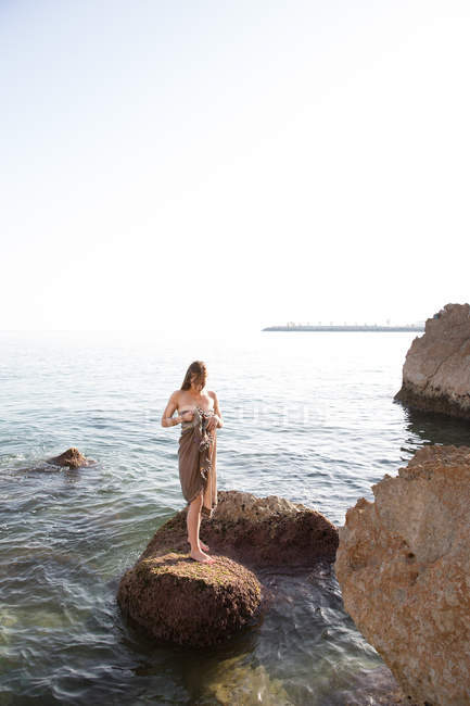 Barefoot woman standing on rock in sea and looking down — Stock Photo