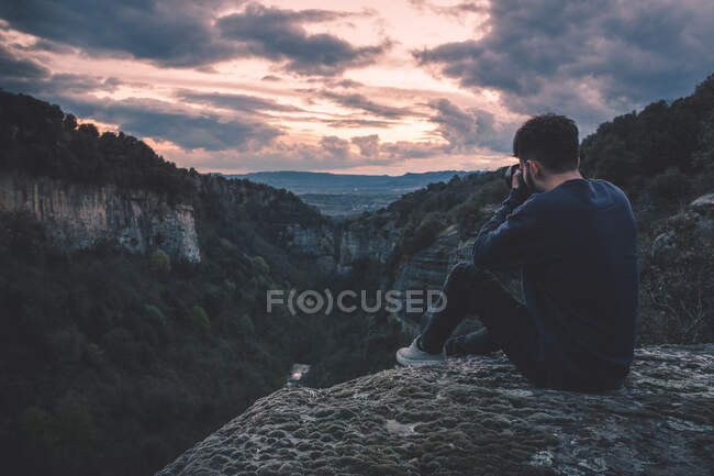 Mann mit Fotokamera sitzt auf Berg mit herrlichem Sonnenuntergang — Stockfoto