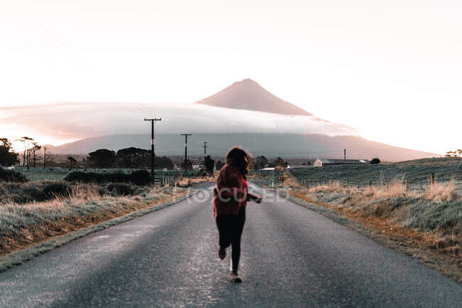 Traveler running on asphalt road near lonely mountain peak with cloud in Taranaki, New Zealand — Stock Photo