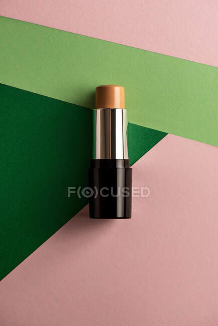 Concealer stick on modern background with geometric shapes. Product and makeup concept from above. — Stock Photo
