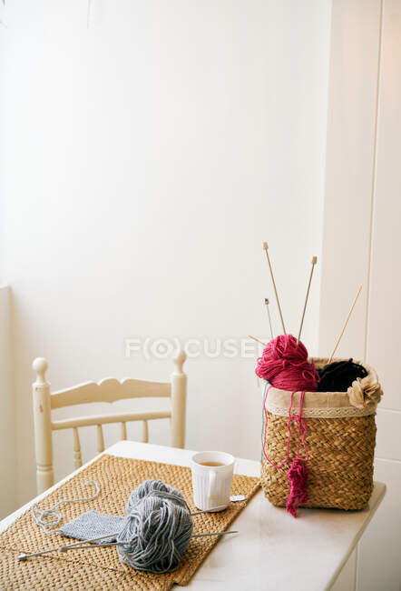 Cup of warm tea placed on table near basket with knitting yarn and needles in cozy room — Stock Photo