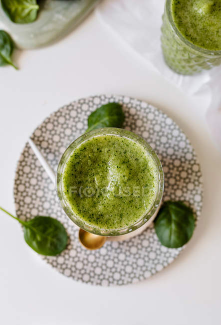Healthy green smoothie of spinach, avocado and kiwi, apple and lemon in glass on patterned plate — Stock Photo