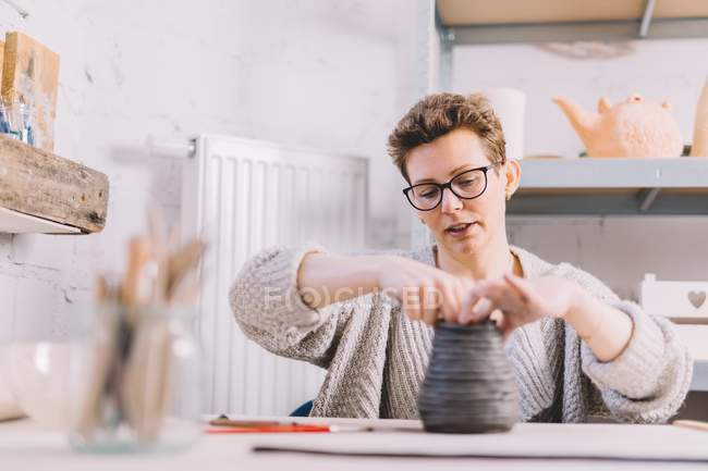 Adult female potter shaping vase from soft clay rolls while sitting at table in workshop — Stock Photo