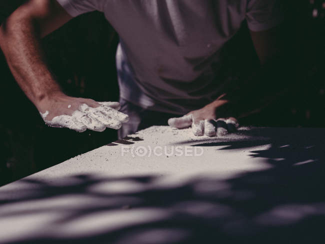 Hands of anonymous male artist spreading rough white plaster on plain surface in workshop — Stock Photo
