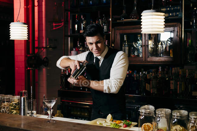 Young elegant barman working behind a bar counter mixing drinks in a shaker — Stock Photo