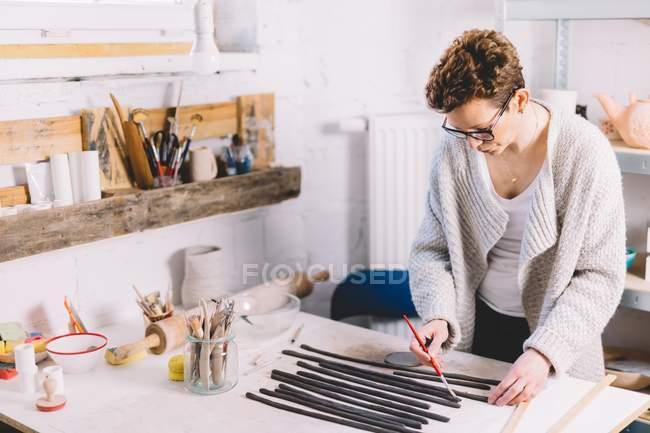 Доросла жінка в окулярах, використовуючи пензель, накриває глиняні кружки водою під час роботи в професійній гончарній майстерні. — стокове фото