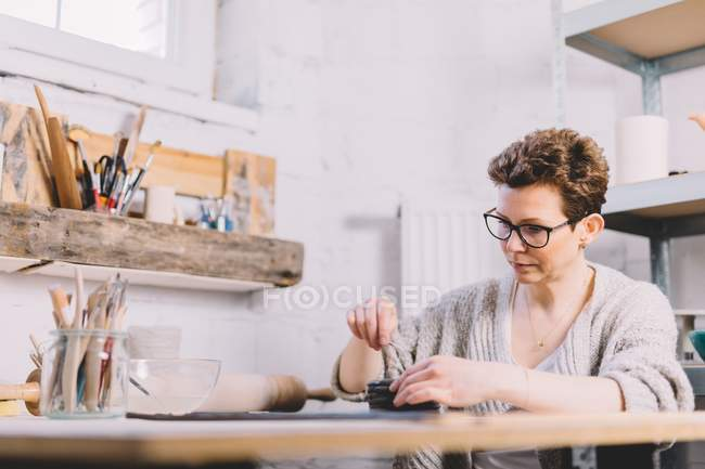 Adult woman in glasses using brush to cover clay rolls with water while working in professional potter workshop — Stock Photo