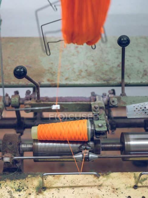 Сучасна промислова машина хитається помаранчевий бавовна нитка на котушку на тканинній фабриці — стокове фото