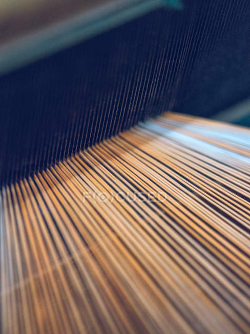 Close-up das linhas brancas e alaranjadas no tear — Fotografia de Stock