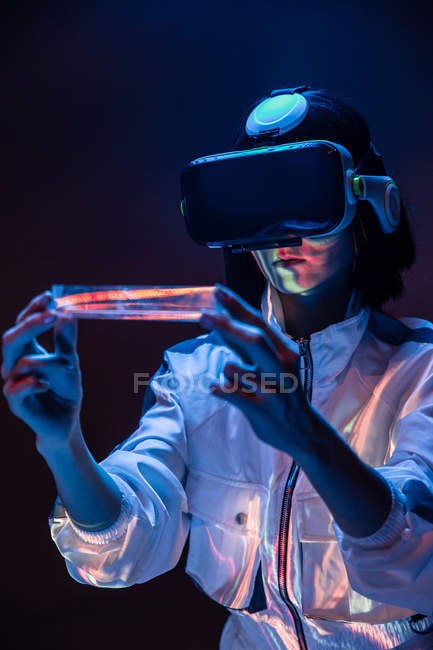 Excited young woman holding prism while having virtual reality experience in neon light — Stock Photo