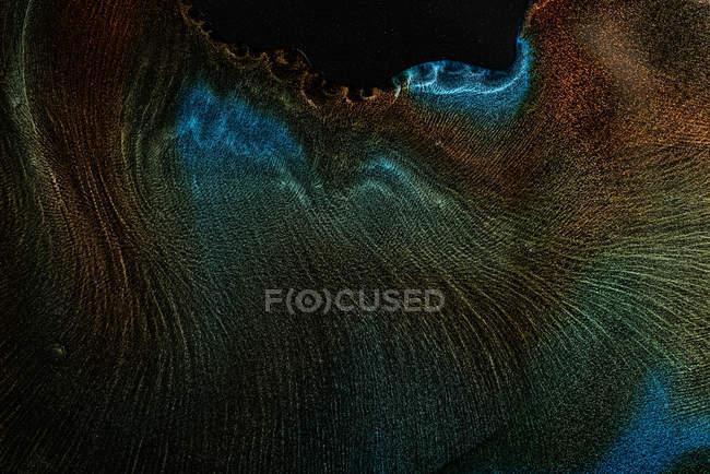 Derrames de mezcla y difusión de colorantes metálicos multicolores sobre fondo negro - foto de stock
