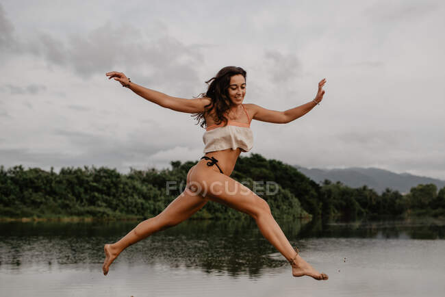 Slim young female in swimwear smiling and leaping over calm water against cloudy sky in countryside — Fotografia de Stock