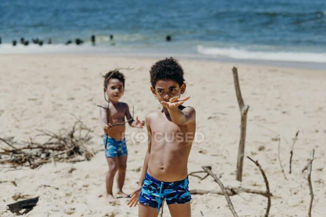 Афроамериканские дети смотрят в камеру и демонстрируют крошечную ракушку, стоя у синего моря — стоковое фото