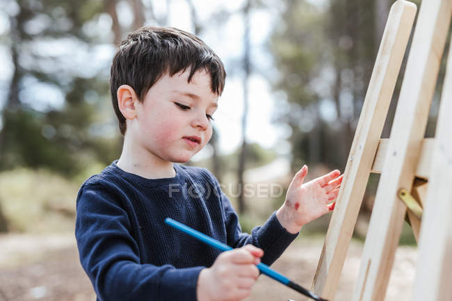 Boy painting on easel in countryside — Stock Photo
