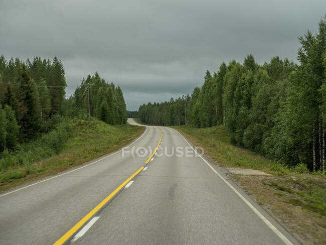Empty asphalt road through green forest in summer cloudy day in Finland — Stock Photo