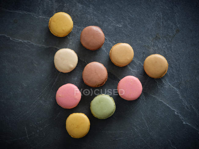 Colorful fresh tasty macaron biscuits placed in triangle shape on grey board — Stock Photo