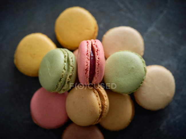 Colorful fresh tasty macaron biscuits in heap on grey board — Stock Photo