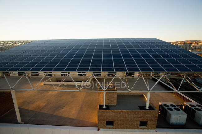 Building with roof made of solar panels under blue sky — Stock Photo