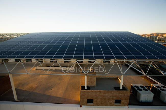 Будівництво з дахом з сонячних панелей під блакитним небом — стокове фото