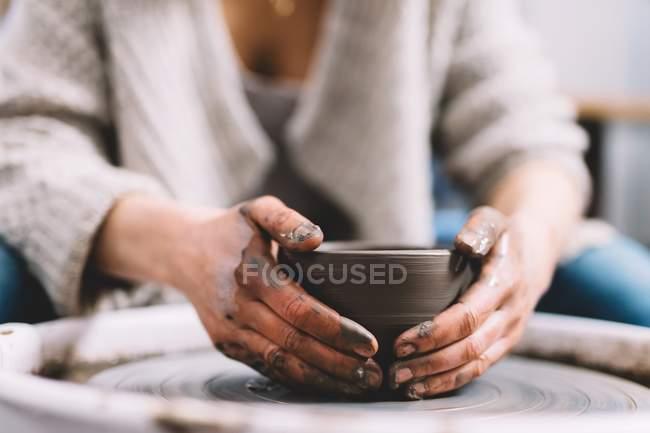 Oleiro fêmea com mãos sujas fazendo panela de barro na roda na oficina — Fotografia de Stock