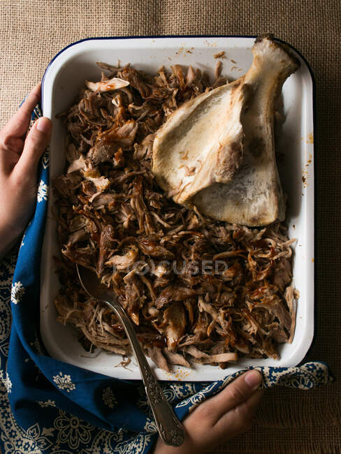 Metal bowl with delicious pulled pork and clean bone placed on ornamental and linen napkins — Stock Photo