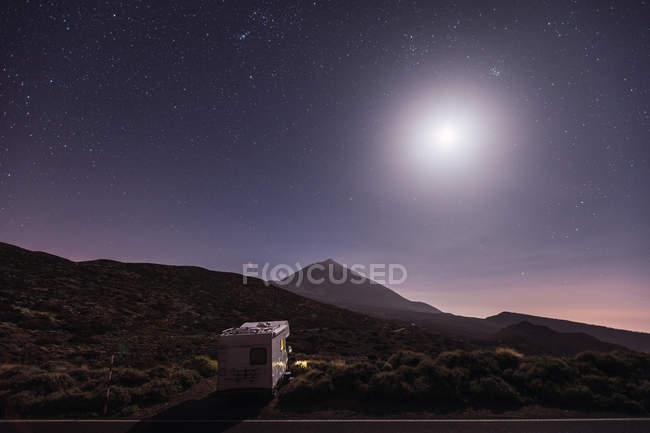 Traveling caravan in desert with bright moon and starry sky — Stock Photo