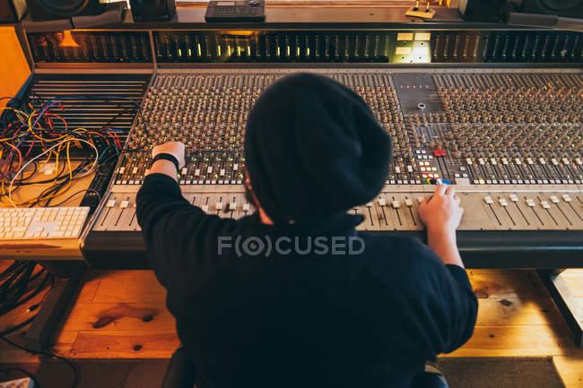 Назад погляд людини, що працює під час гри на вирівнювальному інструменті в студії — стокове фото