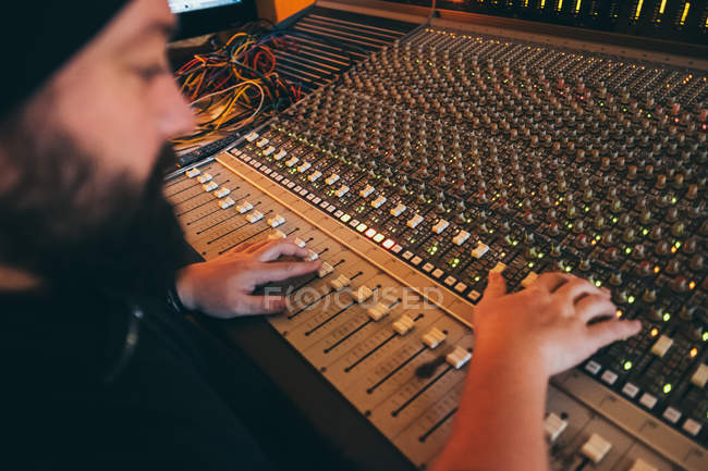 Músico trabalhando enquanto tocava em um instrumento equalizador em um estúdio — Fotografia de Stock
