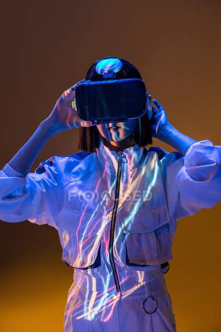 Збуджена молода жінка, що має досвід віртуальної реальності в неоновий світло — стокове фото