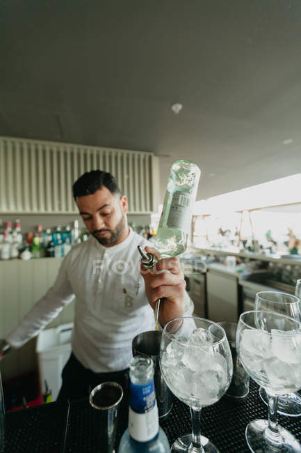 Bartender pouring alcoholic drink to shaker in bar — Stock Photo