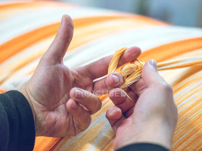 Mãos de pessoa que mantém fios no tear — Fotografia de Stock