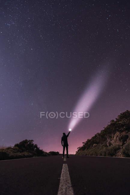 Мандрівник стоячи з факелом в зоряній ночі — стокове фото