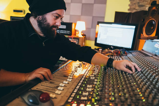 Musician working while playing in a equalizer instrument in a studio — Stock Photo